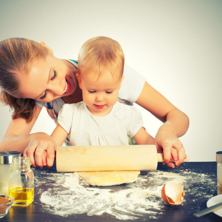 baby girl with her mother rolled out the dough cook bake